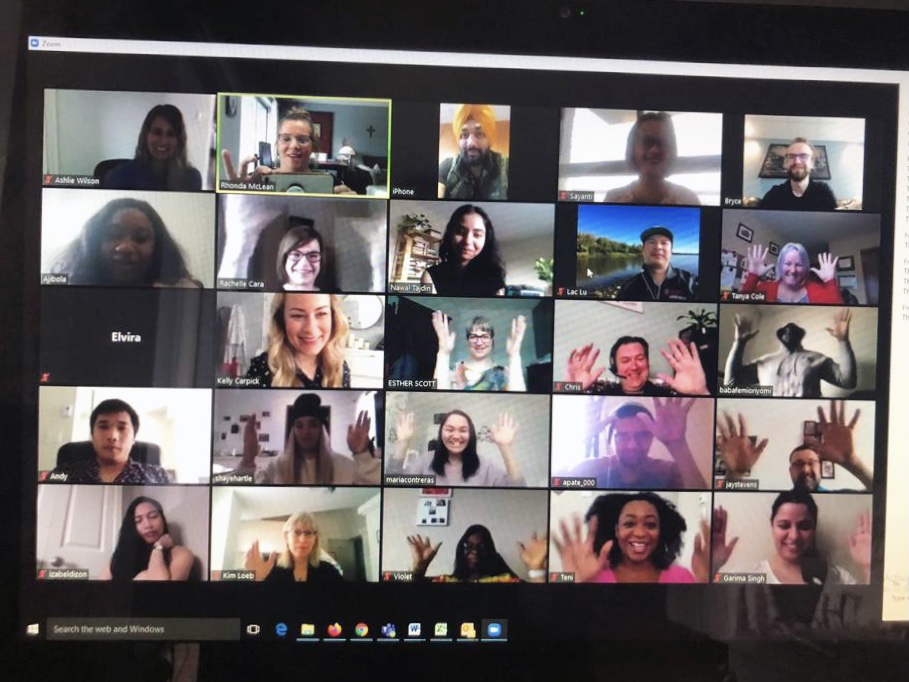 A screen shows 25 participants on a Zoom call, many with their hands in the air in celebration